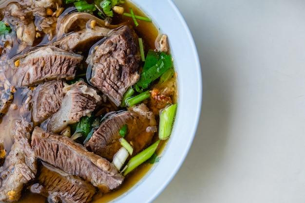 牛肉のスープと肉麺のボウルのクローズアップ