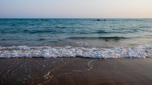 波がビーチの暗い砂の上を洗う