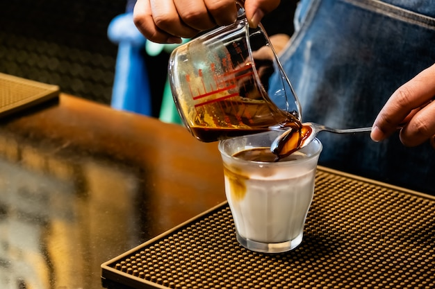 Бариста заваривает кофе, наливает кофе на лед, кокосовое молоко в стакан