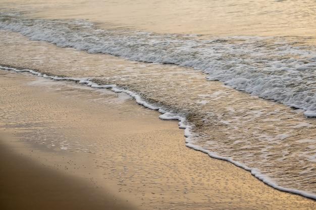 日没時間の砂浜に光沢のある熱帯海の波