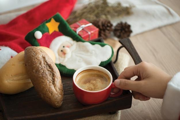 クリスマスの新年にコーヒーのカップを持って手のサンタ。クリスマスリレックスと快適。