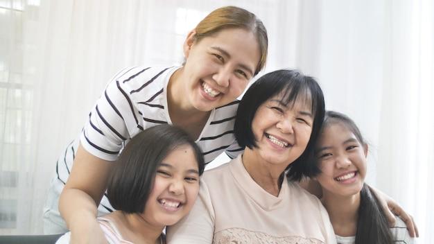 家庭で一緒に笑うアジア人の幸せな家族、女性の多世代