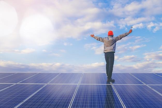 Техник использует ключ для обслуживания электрической системы на панели солнечных батарей