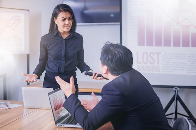 Серьезный босс женщины, ругающий мужчину-работника за плохой бизнес-результат.