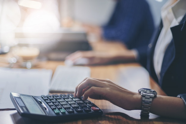 職場で財務報告を計算するために電卓を使用している女性会計士