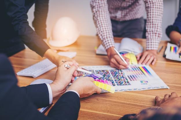 新しいプロジェクトのためのカラーチャートと会議のブレインストームを持つチームデザイナーの作業グラフィック