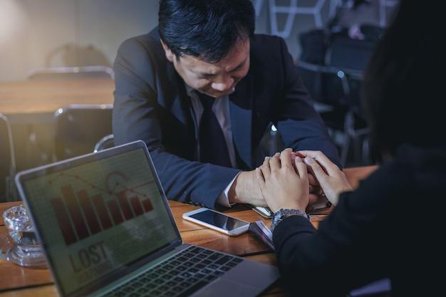 ビジネスの女性は、ビジネス上の損失について同僚を応援し、励ますために手を握ります。