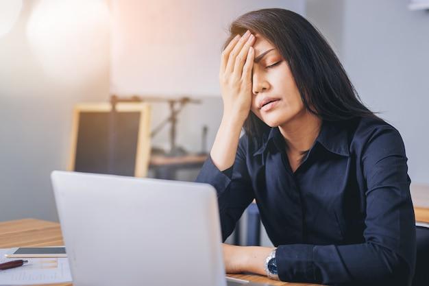 Напряженная коммерсантка работая в офисе утомляла и скучала.