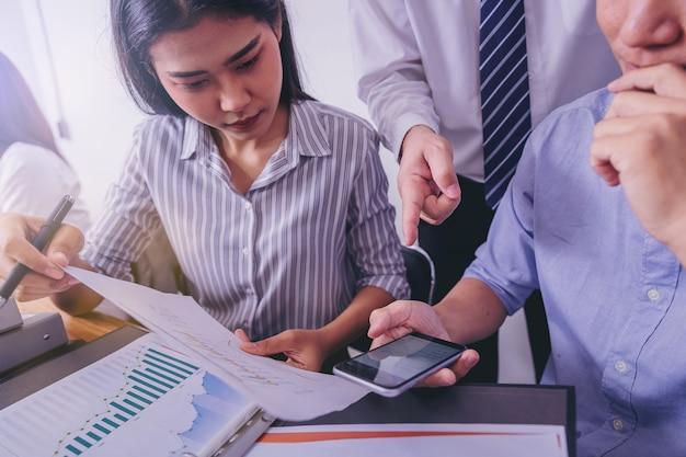 スマートフォンで市場の状況を議論するために会議ビジネス人々。