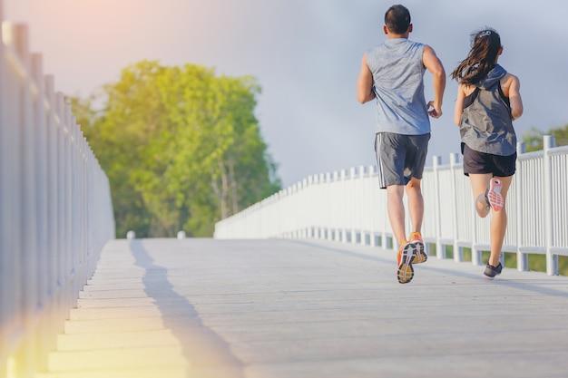 若いカップルが道路上で全力疾走を実行しています。屋外トレーニング中にフィットランナーフィットネスランナー