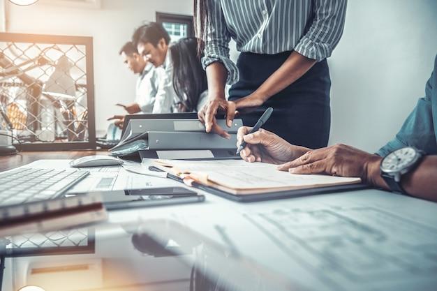 Архитекторы обсуждают данные, работая над эскизами архитектурного проекта на строительной площадке за столом в офисе