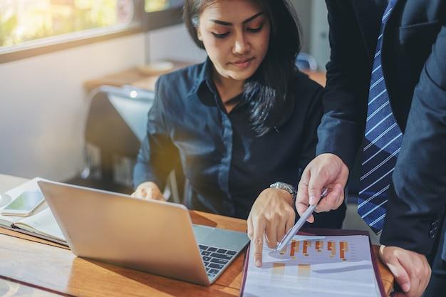 ラップトップを扱う若い魅力的なビジネス女性は彼女の同僚によって導かれています。