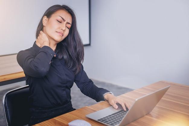 ラップトップでの作業から痛みを伴う首のために苦しんでいる働く女性の顔