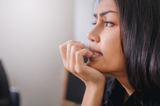 Слабонервная коммерсантка сдерживая ее ногти с эмоцией беспокойства в офисе.