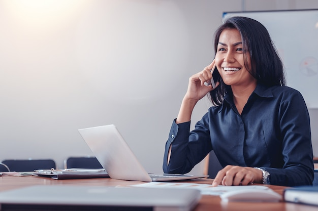 オフィスで携帯電話で話している黒いシャツの女性実業家