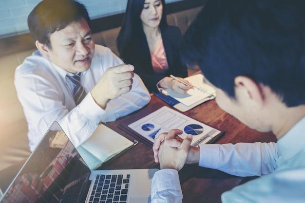 上司としてビジネスマンのオフィスでのビジネス会議中にビジネスのミスのために彼の従業員を非難