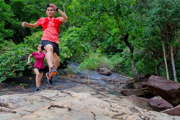 カップルが丘を走ってトレイルでジャンプ
