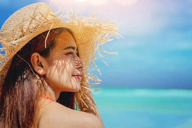 きれいな女性の自由の休暇は暖かい光で海で楽しむリラックス