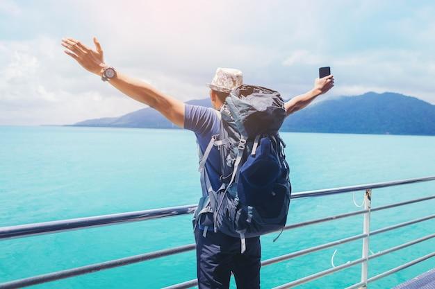 Красавец с смартфон распростертыми объятиями праздновать его праздник свободы во время путешествия на круизном судне.