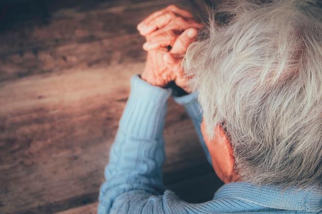 Старый человек молится за руку. концепция: надежда, вера, драматическое одиночество, грусть, депрессия, плач, разочарование, здравоохранение, боль.
