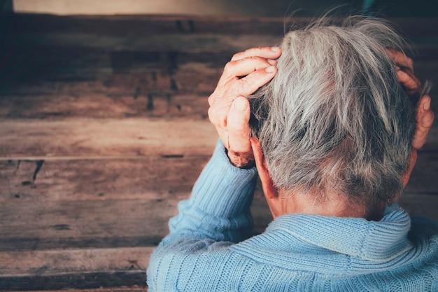 大人の女性は頭痛がします。彼女は暗い黒い部屋に手で頭を座っています。コンセプト劇的な孤独、悲しみ、うつ病、悲しい感情、泣く、失望、ヘルスケア、痛み。