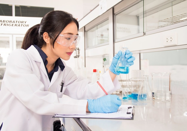 Интерьер чистой современной белой медицинской или химической лаборатории. ученый лаборатории работая на лаборатории с пробирками и отчетом. концепция лаборатории с азиатской женщиной химик.