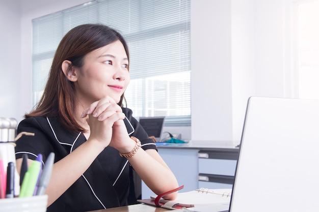 Азиатская женщина счастлива, сидя на рабочем месте в офисе.