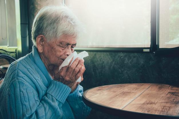 家のインテリアにティッシュで口を覆っている咳の老人。彼女はインフルエンザ、アレルギー症状、急性気管支炎、肺感染症または肺炎を患っています。