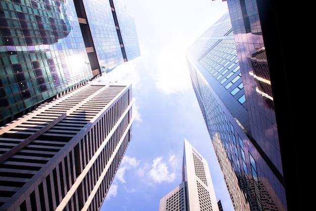 Нижний взгляд современных небоскребов / офисных зданий в финансовом районе городов сингапура против голубого неба. экономика, финансы, концепция деловой активности. скопируйте место для содержимого.