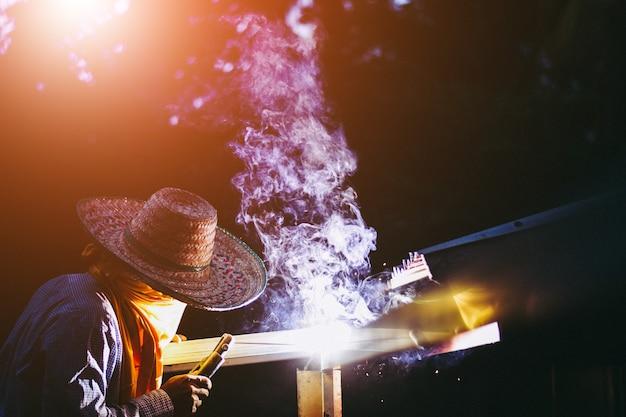 Работник молодого человека сваривая железные части на работе с защитными очками