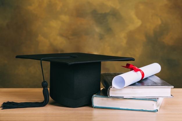 卒業の概念。卒業の帽子、学位論文と木のテーブルの本