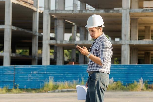 安全なエンジニアヘルメットの若いエンジニアは、携帯電話を使用して、または建設現場でメッセージを送る。