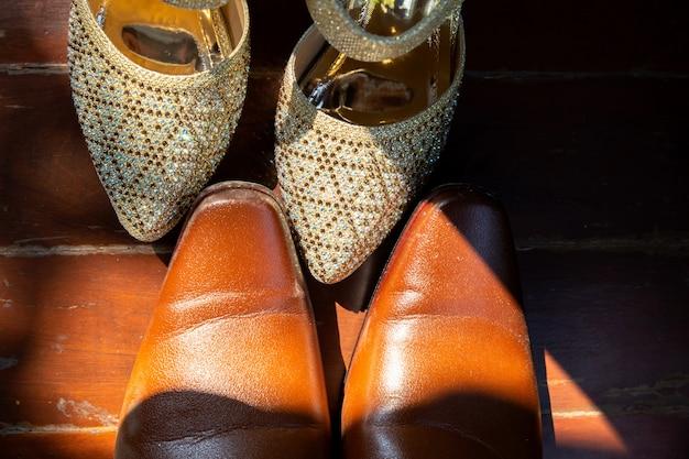 Коричневые ботинки жениха и белые ботинки невесты ставят на деревянный фон
