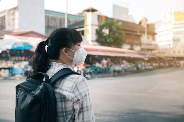 市内の大気汚染のためのマスクを持つ女性