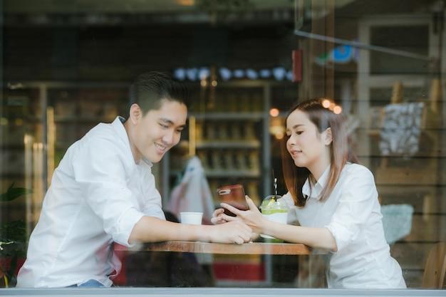 Азиатские пары, проверка телефона вместе, сидя в кафе, выпить кофе. день святого валентина