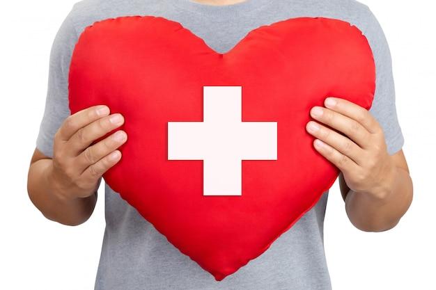 Красное сердце со знаком креста в мужской руке, крупный план. международный день красного креста
