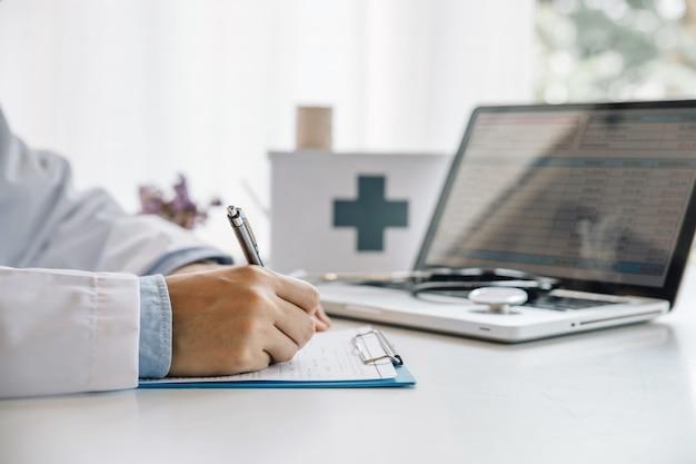 医者は病院のオフィスの机に座っている間医療フォームを記入します。職場の医師