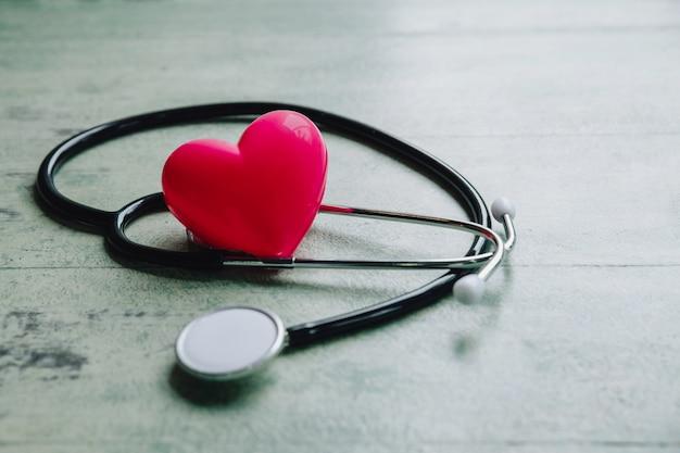 世界保健デー、赤いハートと古い木製のテーブルの上の聴診器
