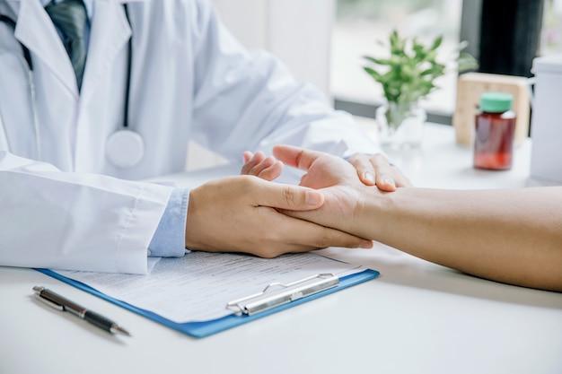 医師は医療室で患者の血圧をチェックしています
