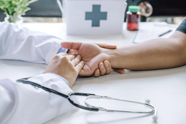 男性患者と聴診器を安心させる医師の手