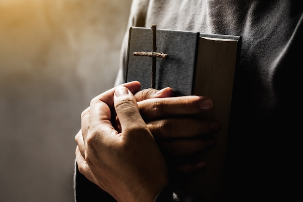 聖書と神からの祝福の十字架を持っている女性宗教概念の女性