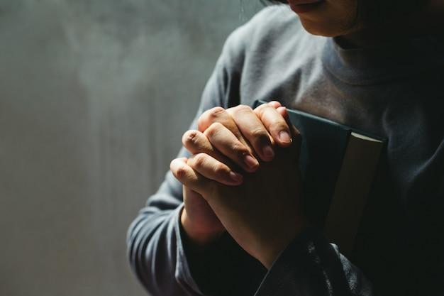 Женщины в религиозных понятиях руки, молящиеся богу. женщины, держащие библию, да благословят бога