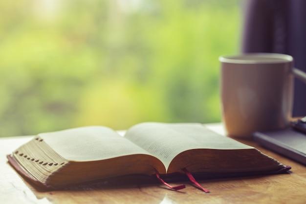 窓の光と木製のテーブルに朝の献身のためのコーヒーカップと聖書を開く
