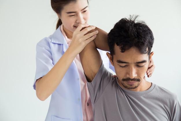 男性に肩のマッサージを与えるプロの女性理学療法士。