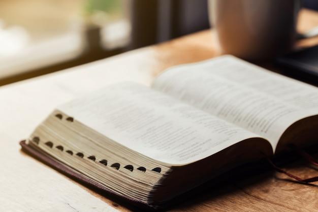 木製テーブルの上の朝の献身のためのコーヒーカップと聖書を開く