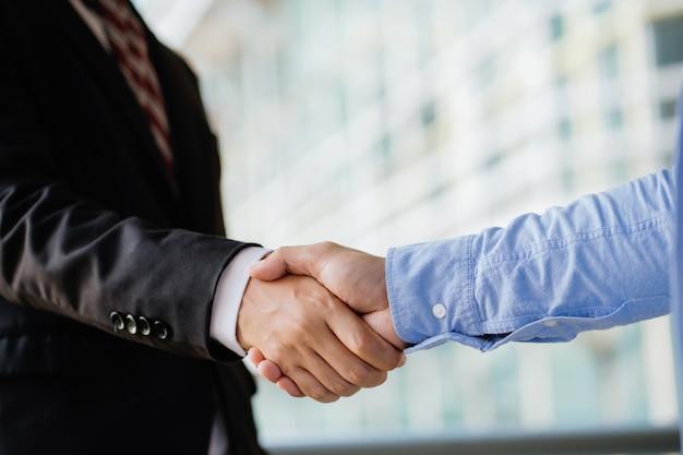 Деловые люди пожимают друг другу руки, заканчивают встречу. успех совместной работы, партнерства и рукопожатия