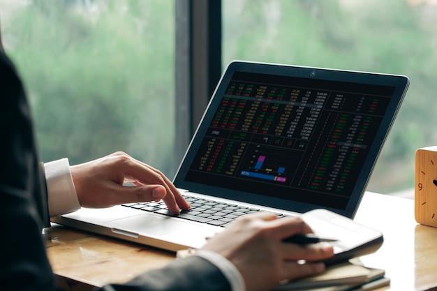 ビジネスの男性またはビジネスドキュメントとオフィスのテーブル上の電卓を持つラップトップコンピューターに取り組んでいる会計士