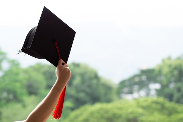 Выпускной день, поднимая руки с выпускным колпачком. начальный день, поздравление