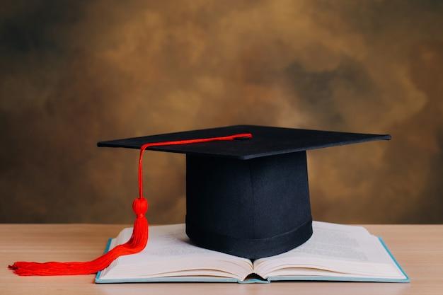 開いているブックの卒業キャップ。教育コンセプト。卒業の日