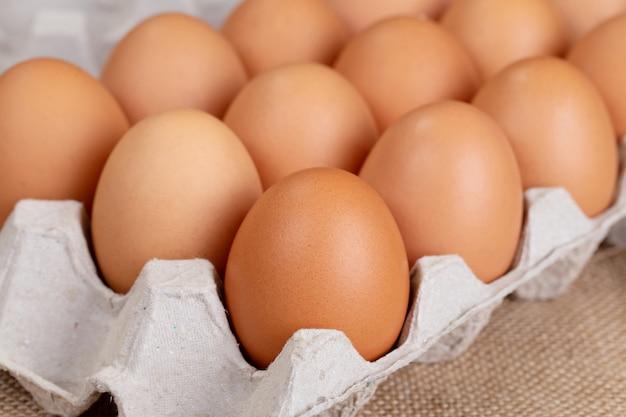 Яйцо, куриное яйцо. яйца в картонной коробке на ткани.